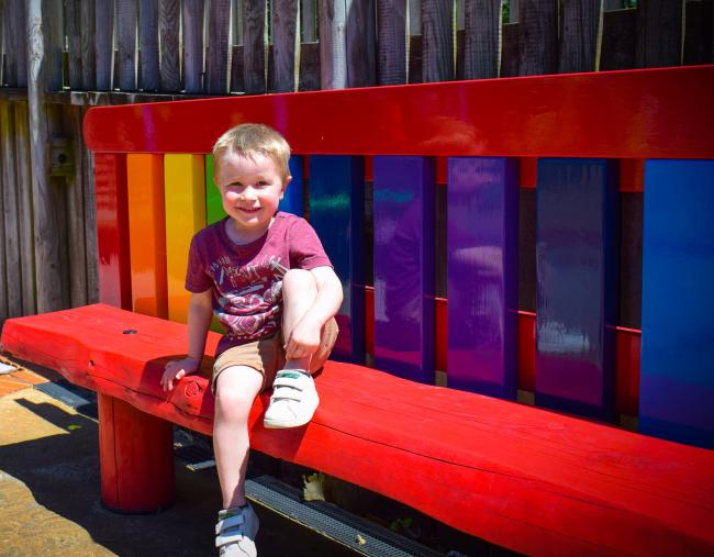 Noah, aged three, sits on Drusillas new Buddy Bench