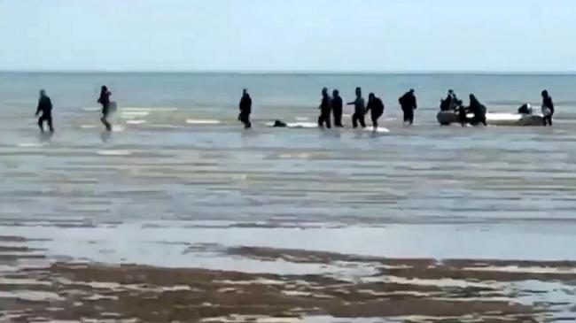Video grab of a group of migrants coming ashore on Greatstone beach in Littlestone, Kent, after crossing the Channel . The group are some of a 100 that reportedly reached British waters yesterday. September 10 2019.  See National News story NNmigrants. A
