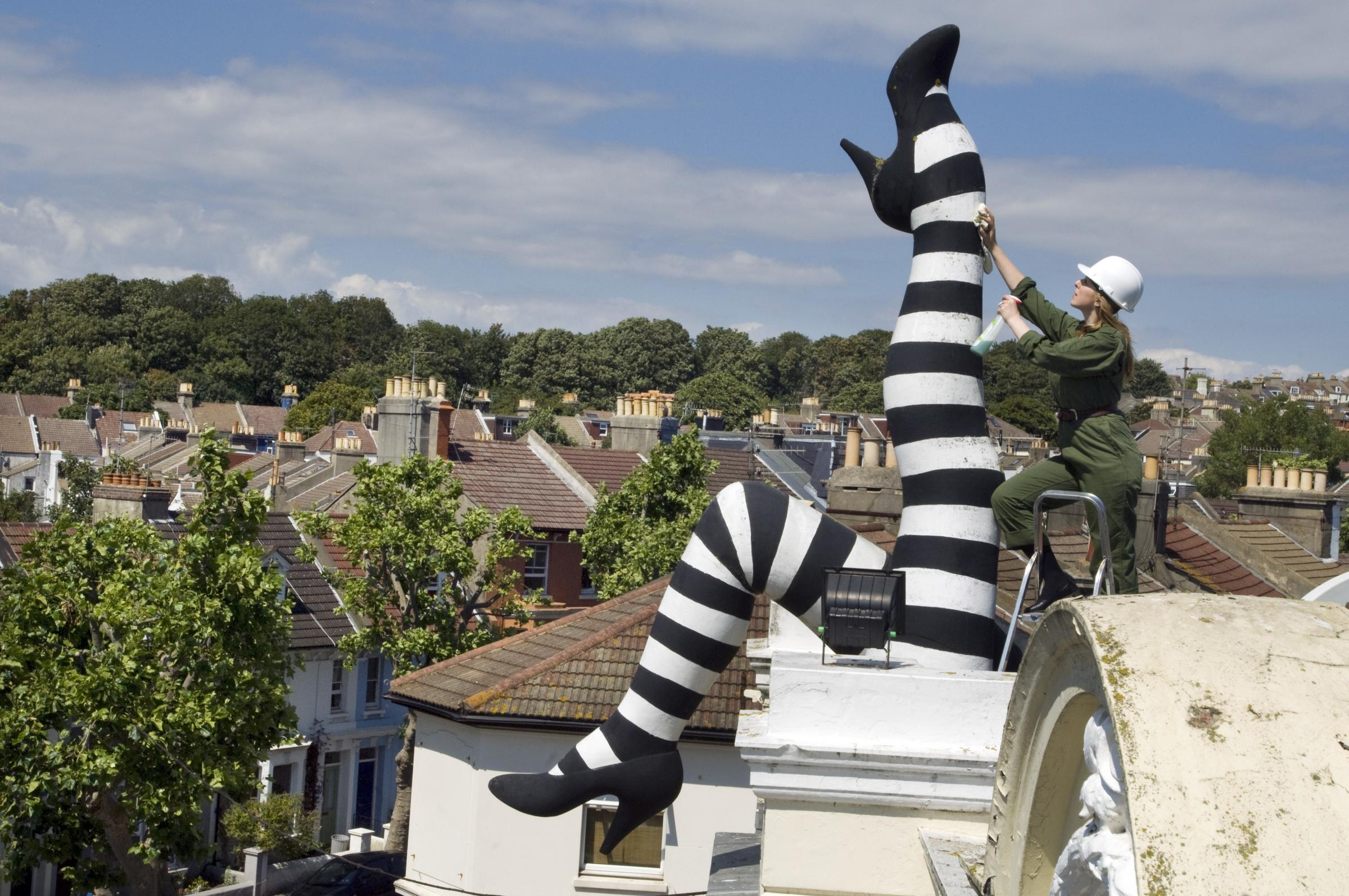 Picture by Roger Bamber:20 July 2010:Duke of Yorks cinema duty manager Emily Eastwood cleans the iconic sculptured striped legs on the roof of the Duke of Yorks cinema in Brighton, East Sussex, England UK. The Cinema celebrates its Centenary on 22
