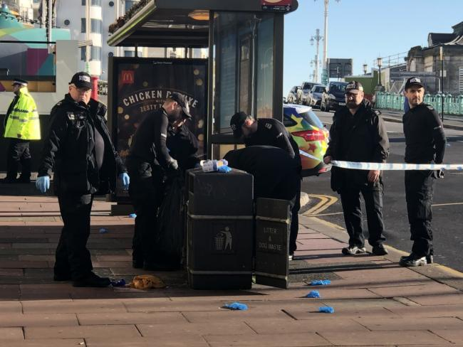 Police search bins at murder scene as seafront road remains closed