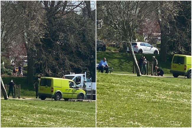 Hove park council staff stand closely together to tape off outdoor gym equipment