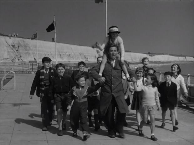 The Argus: The children and Mr Butterworth parade by Black Rock lido, with Sue Downey on the future Carry On star's shoulders. Photo British Film Institute.png