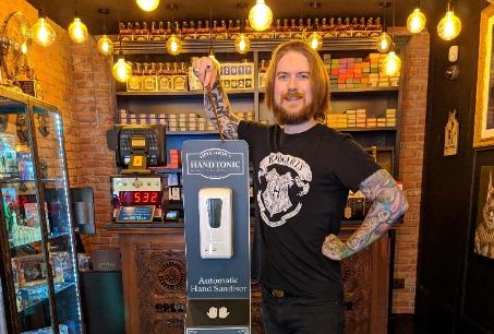 Oliver Dall with the shop's new hand sanitiser station