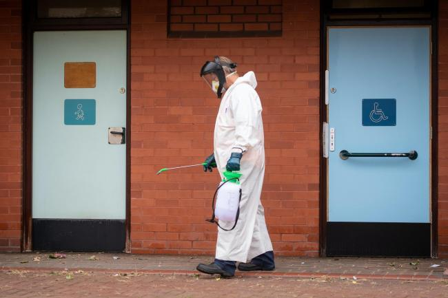 A worker for Leicester City Council disinfects public toilets