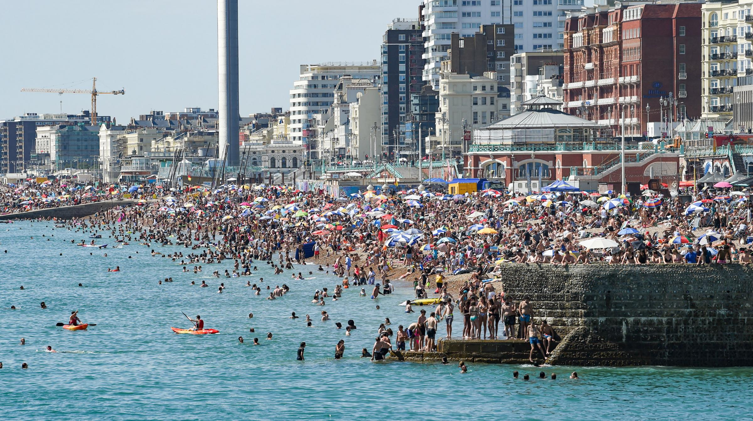 Brighton UK 7th August 2020 - Crowds flock to Brighton beach as they enjoy the sunshine on what has been predicted to be the hottest day of the year so far with temperatures reaching the high 30 in some parts of the South East today : Credit Simon Dack /