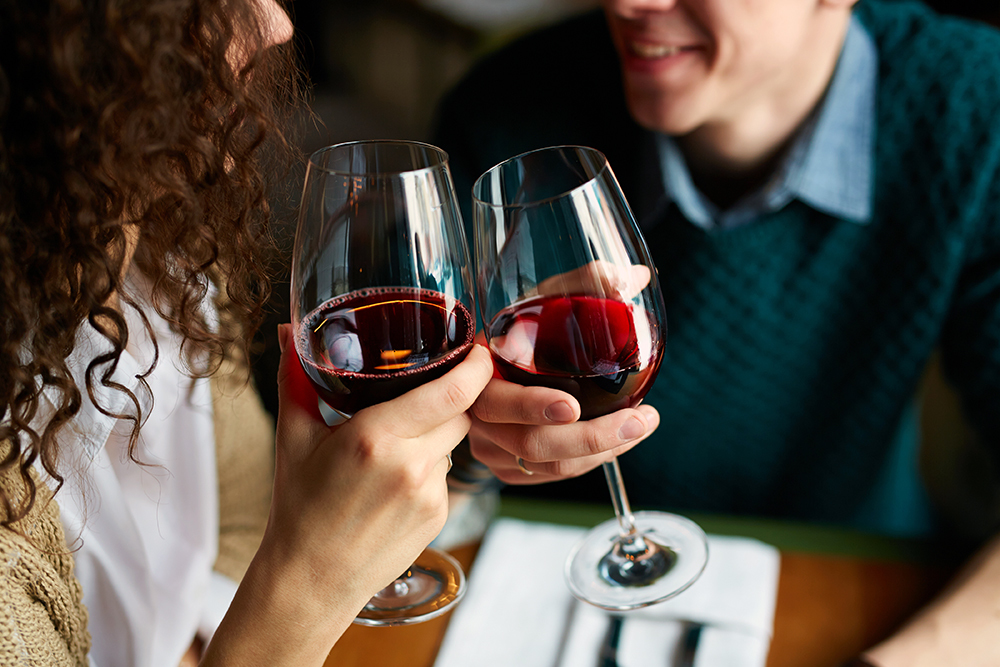 Amorous couple toasting with red wine in restaurant.