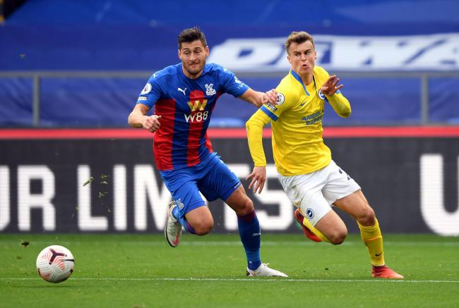 Solly March and Crystal Palace's Joel Ward race towards to the ball