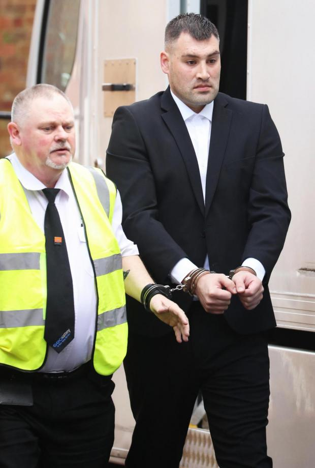 The Argus: Michael Roe in a black suit, wearing handcuffs