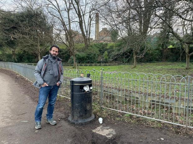 The Argus: Hove Park Ward Councillor Samer Bagaeen next to an overflowing bin in Hove Park