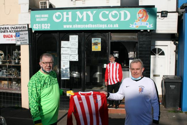Chairman, Phil Aspinall (left) and club treasurer Howard Whitelaw (right) holding the new shirt, as sponsor Ali Yukselir looks on from outside his chip shop