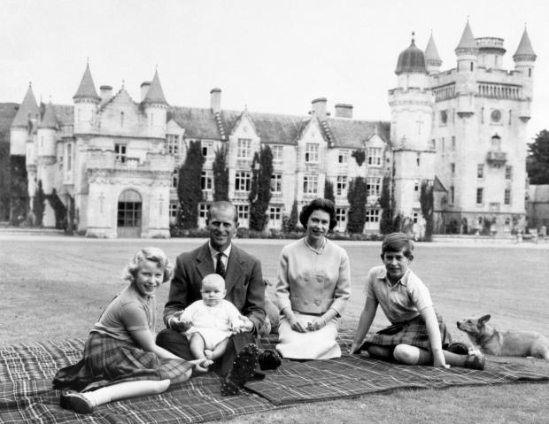 The Argus: The Queen, the Duke of Edinburgh and three of their children Princess Anne, Prince Charles and baby Prince Andrew, on his father's knees on the lawns at Balmoral in 1960