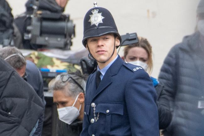 Harry Styles is seen shooting scenes for his new film The Policeman which also stars Emma Corrin.