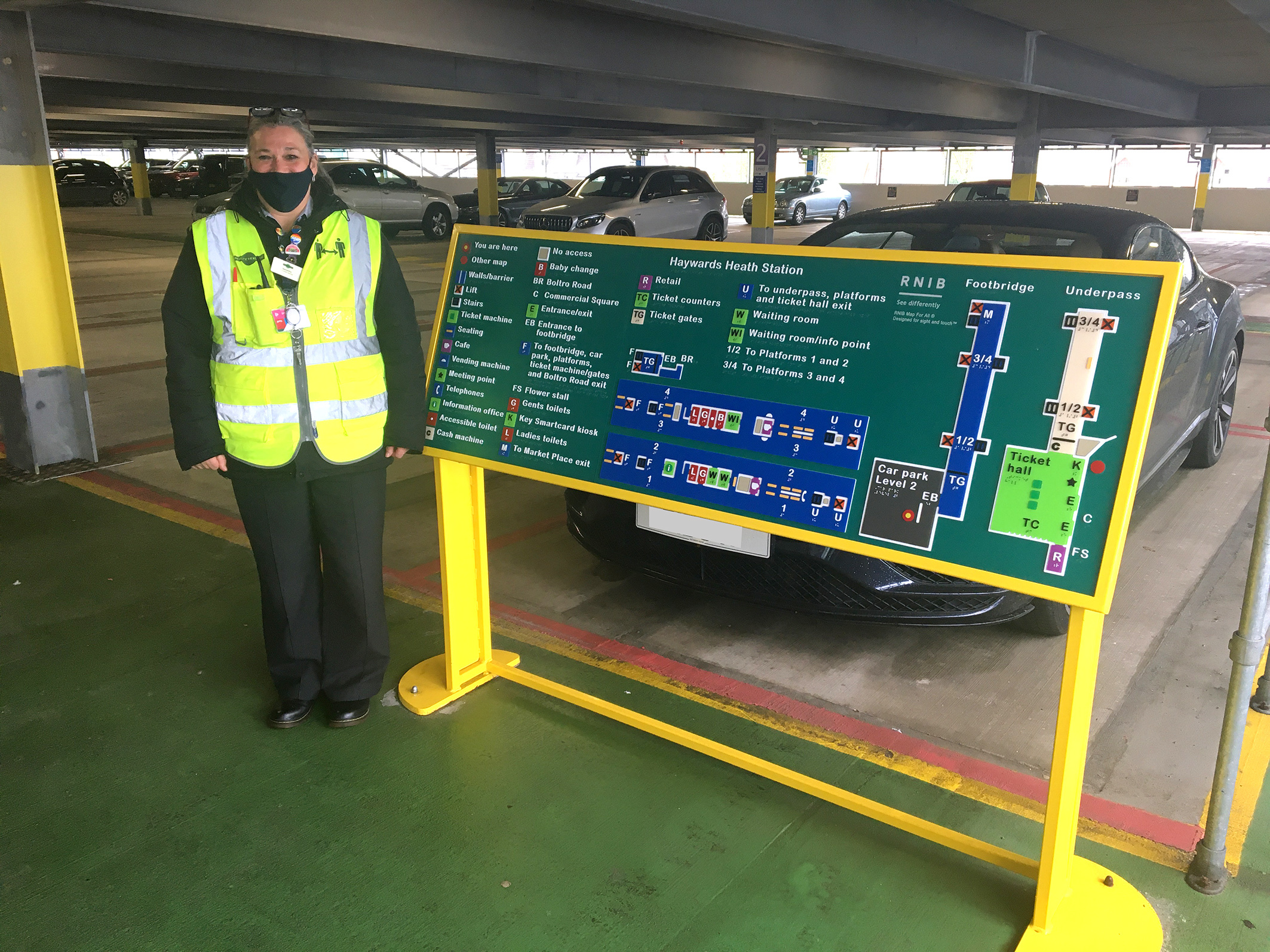 Heywards Heath - Staff member Sam Hugit next to a map touching the parking lot 2