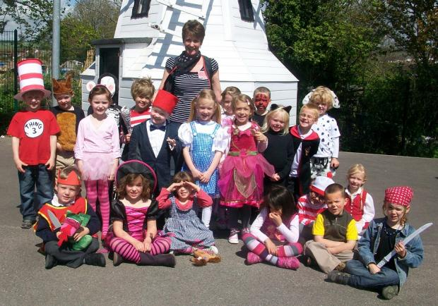 Headteacher Margaret Enoch with pupils in book-inspired costumes