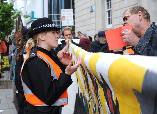 A protester speaks to a police officer outside Barclays in Brighton