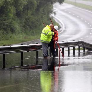 Workers survey the water on the A33, which is closed due to flooding in Chineham near Bassingstoke, Hampshire