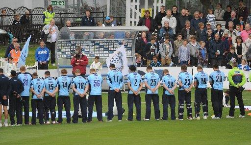 Tribute: Players and supporters stand in silence to remember Tom Maynard last night. Picture by Simon Dack