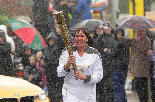 Gabriella Broadhurst carries the Olympic Flame in heavy rain on the Torch Relay leg between Bognor Regis and Westergate