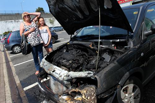 The shocked driver with her granddaughter next to their burnt out car