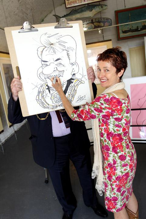 SKILL: Artist Susan Harrison holds up the caricature of Bill Randall
