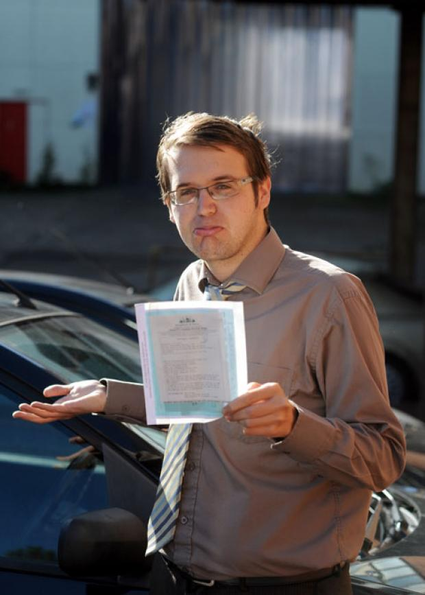 Tim looks fed up after receiving a parking ticket