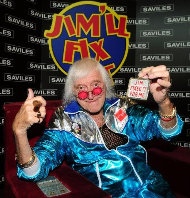 Jimmy Savile holds a badge while sittin in the Jim'll Fix It chair