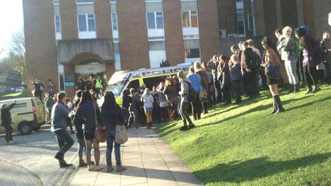 Students crowd around a police van where MP Mike Weatherley was sheltering