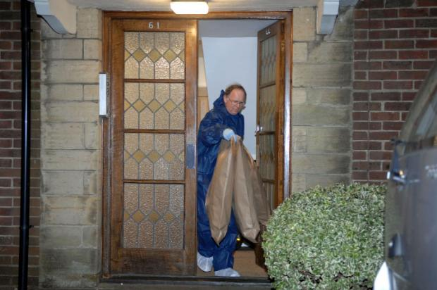 Scenes of crime officers gather evidence at the couple's flat in Hove