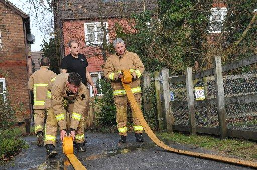 Firefighters pump water from a burst main away from Richard Murray's home