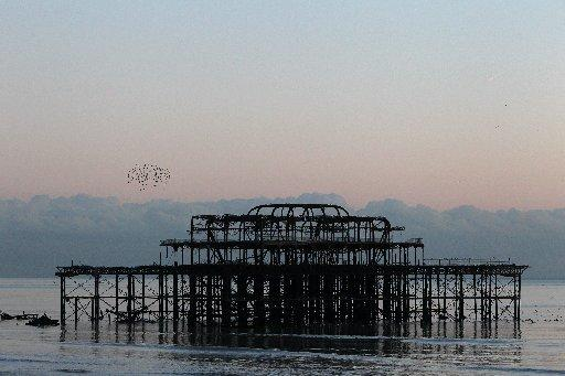 A small group of starlings flying over the West Pier on Tuesday, December 11
