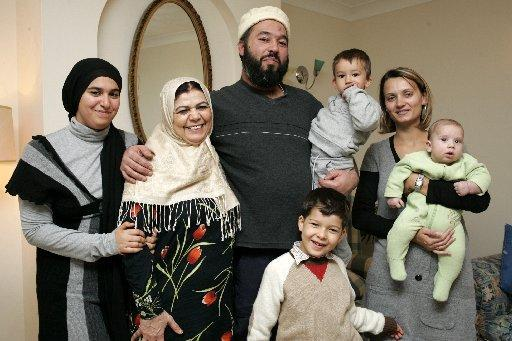 The Argus: Mother Zohra Zewawi, 65, (2ND LEFT) and Omar's brother Abubaker Deghayes, 39, (3RD FROM LEFT) holding Taleb Deghayes, 2, celebrate the news that Guantanamo detainee Omar Deghayes, 38, is on his way home after five years held in the camp. They are pictured at the family home in Saltdean with Abubaker Deghayes daughter Aisha Deghayes, 15, (1ST LEFT) Tamara Deghayes (RIGHT) holding Taha, 3 months, and Ziko Deghayes, 6, (FRONT)