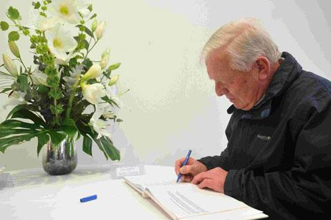 Arthur Hart signs the book of condolence at Sussex County Cricket Club in memory of Christopher Martin-Jenkins and Tony Greig