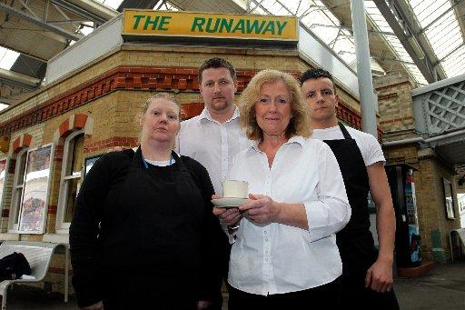 Jaqueline Elsey (holding tea) with her team outside The Runaway at Lewes Station