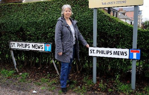 Historian Averil Older next to the St Phillip's Mews signs that are missing an apostrophe