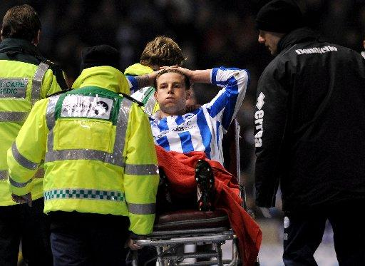 Will Hoskins is taken away on a stretcher after injuring his knee against Blackburn