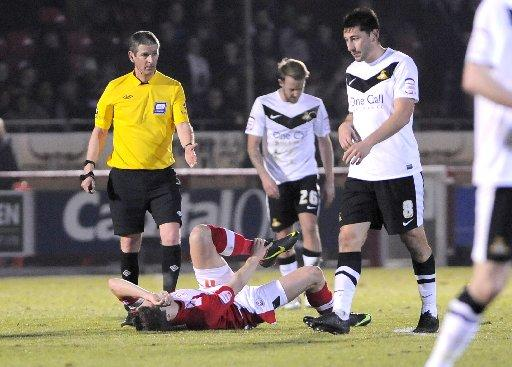 Josh Simpson lies on the floor after injuring his ankle against Donaster