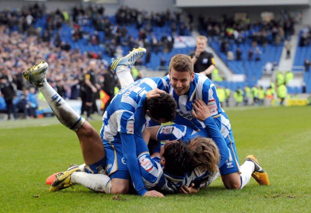 Leo Ulloa is mobbed after completing his hat-trick (photos Simon Dack)