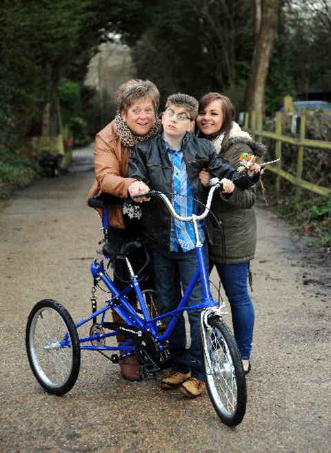 Adam Barnard with mother Annette, sister Lynda and the new bike