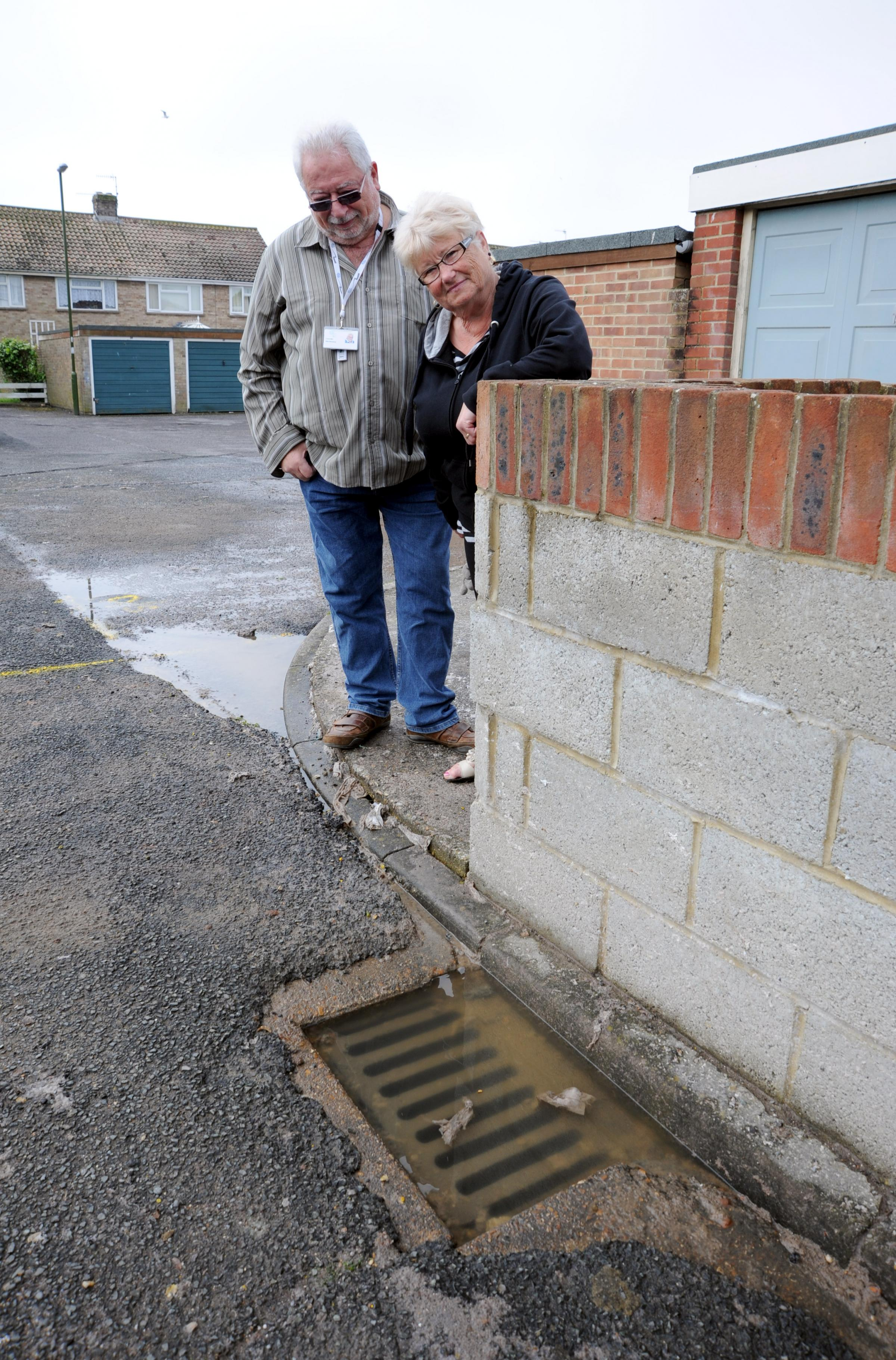 Resident Pat Tough shows Adur Cllr Mike Mendoza the overflowing storm drain problem at St Giles Close