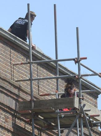 Masked woman scales scaffolding