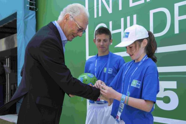 Megan places a Football For Friendship bracelet on German legend Franz Beckenbauer's wrist as part of her prize
