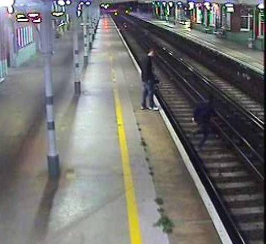 Shocking footage of three men jumping onto railway line just minutes before a train