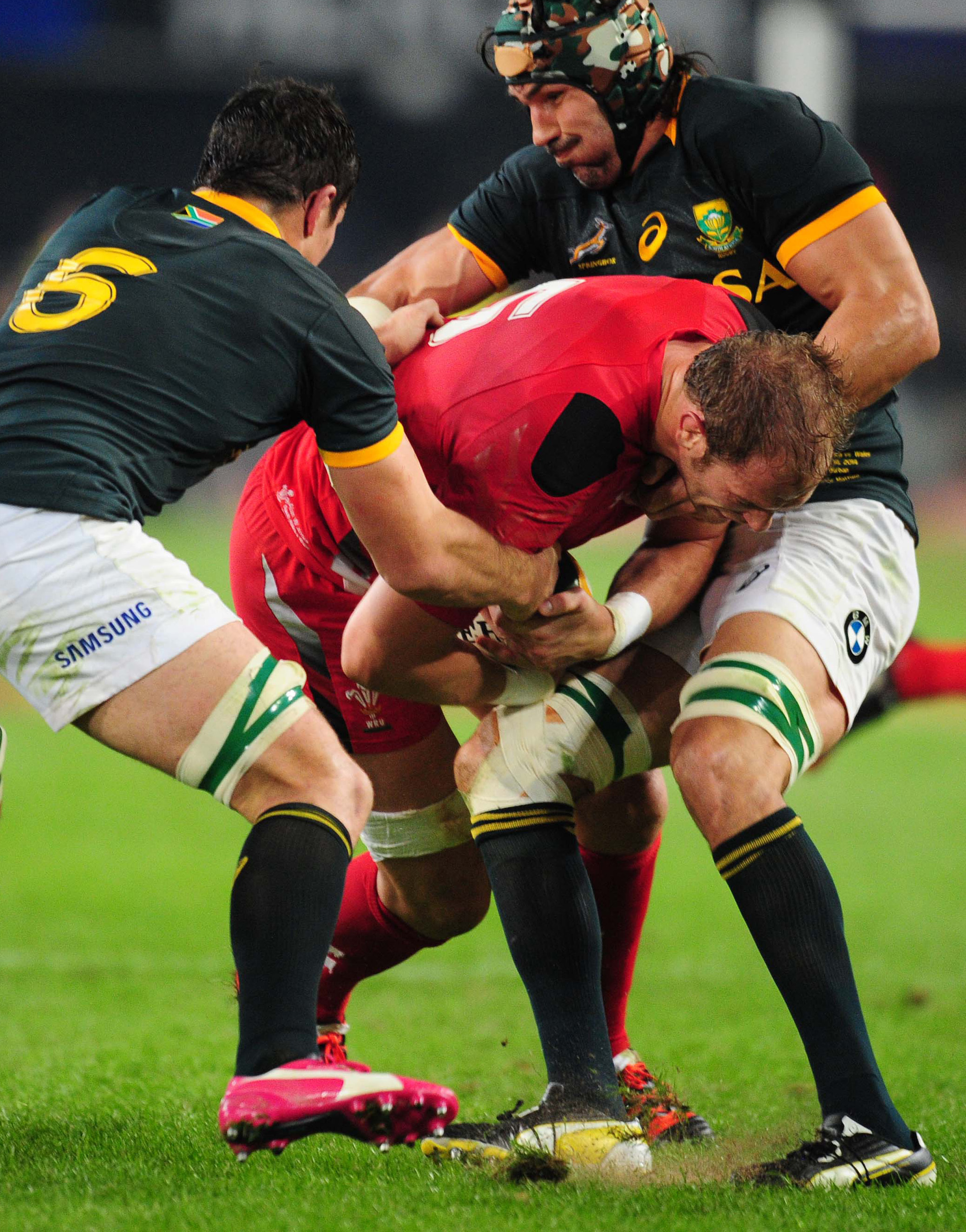 Wales' Alun-Wyn Jones, center, is tackled by South Africa's Francois Louw, left, and Victor Matfield, right, during their Rugby test match in Durban, South Africa, Saturday, June 14, 2014.