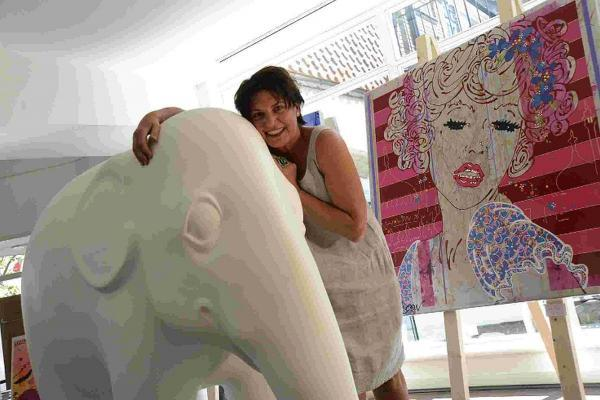 The Argus: Artist Louise Dear pictured at her pop-up shop in Brighton Square with Tinkle, an elephant she painted to raise money for a charity called Elephant Family