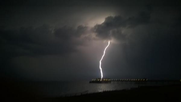 Spectacular thunderstorm strikes house and is seen over pier