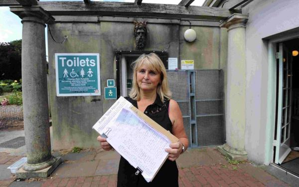 Café worker Mary Lemon with the petition and, inset, a sign saying the toilets belong to the council, not the café