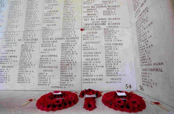 Red poppy wreaths are placed near names of the missing on the Menin Gate in Ypres, Belgium