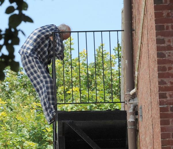A man clings to the fire escape outside Princess Alexandra House in Preston Park Avenue
