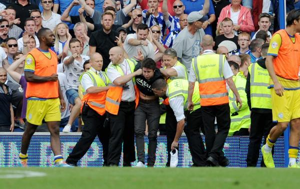 Stewards deal with the pitch invader