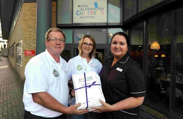 Andrew Hinton and Sally Austin from Charity Roadtrip hand over the pack to Royal Alex head of nursing Lorraine Tinker